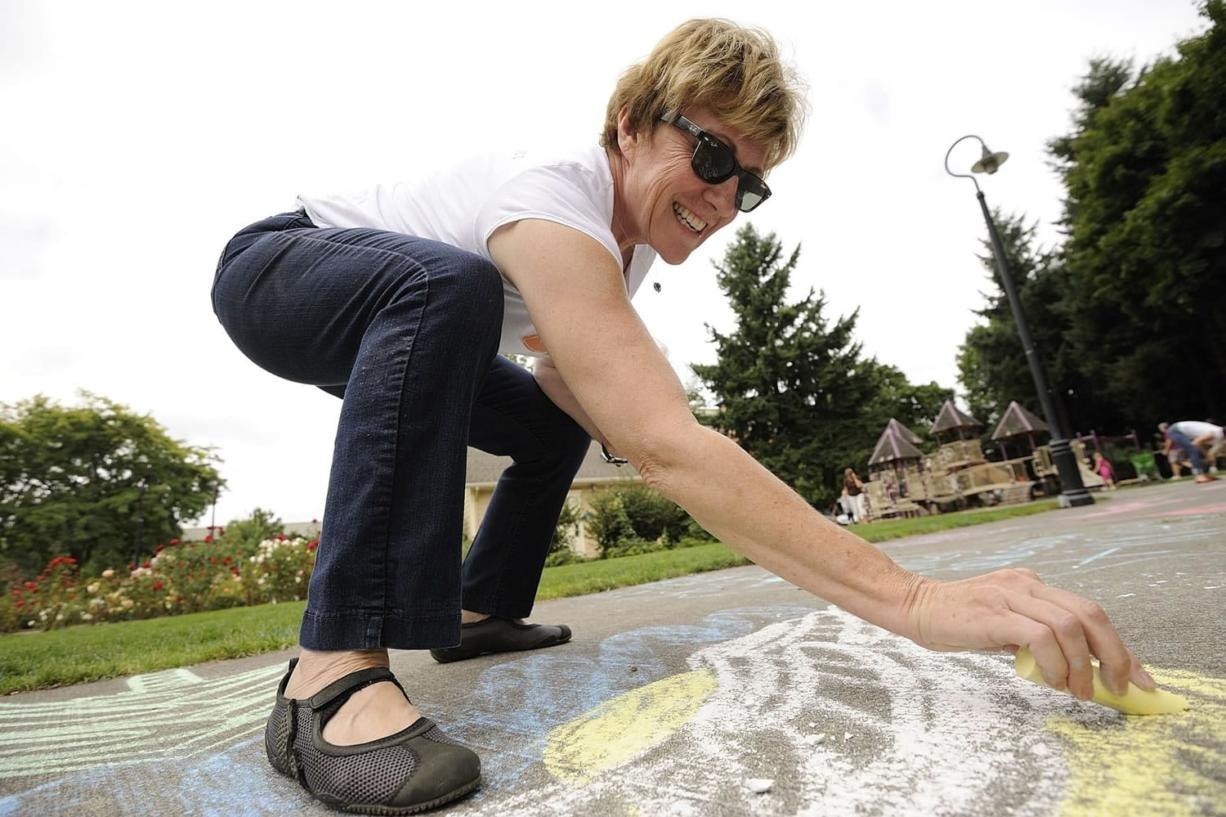 Debbie Oliver, co-founder of Be the Gift, fashions her message during Chalk the Walks in Esther Short Park. Almost half of the U.S. states are participating in the campaign, said Michele Larsen, one of the event's founders.