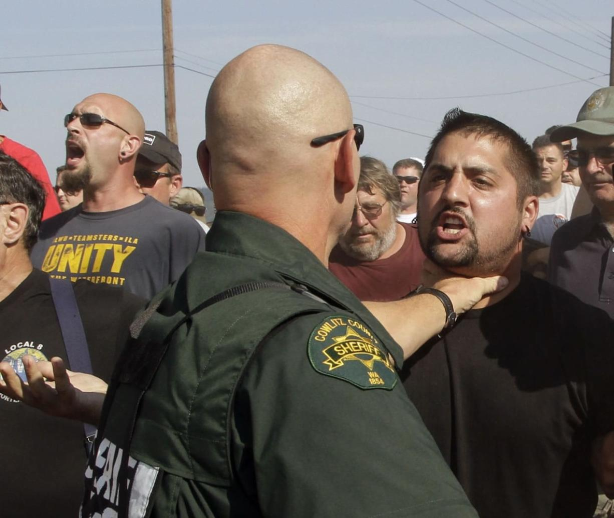 A Cowlitz County Sheriff grabs a union worker by the throat as police move in on several hundred union workers blocking a grain train in Longview on Wednesday
