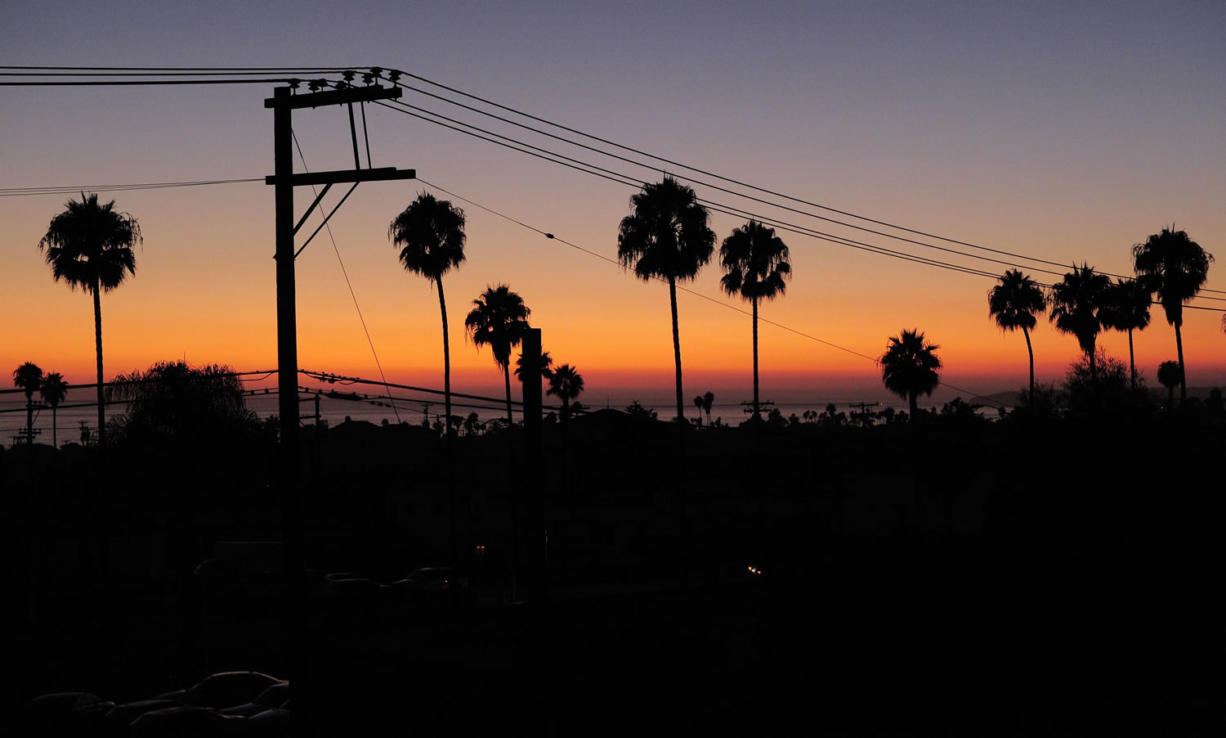 The sun sets Thursday in San Clemente, Calif. as homes sit below in the darkness during a power outage. There were no catastrophes caused by the widespread outage that knocked out power in a region with a population of nearly 6 million spanning both sides of the U.S.-Mexico border.