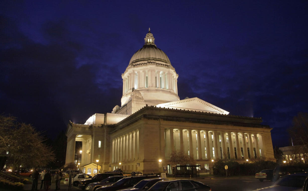 The Washington state Capitol is lit against a late-evening sky in Olympia.