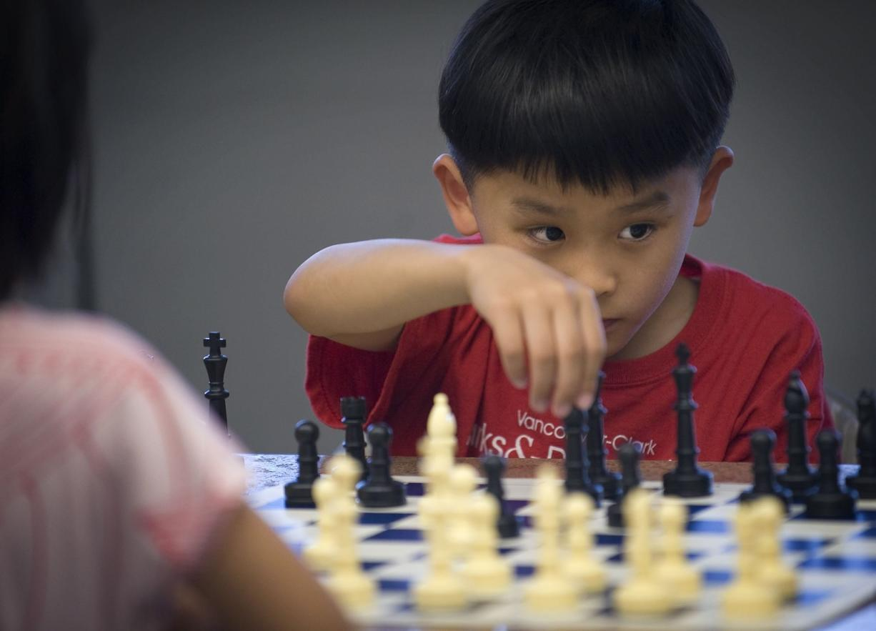 Jason Chang, 7, contemplates his next move while playing Plunder Chess against Alice Tang, 6, at EinsteinWise in east Vancouver.
