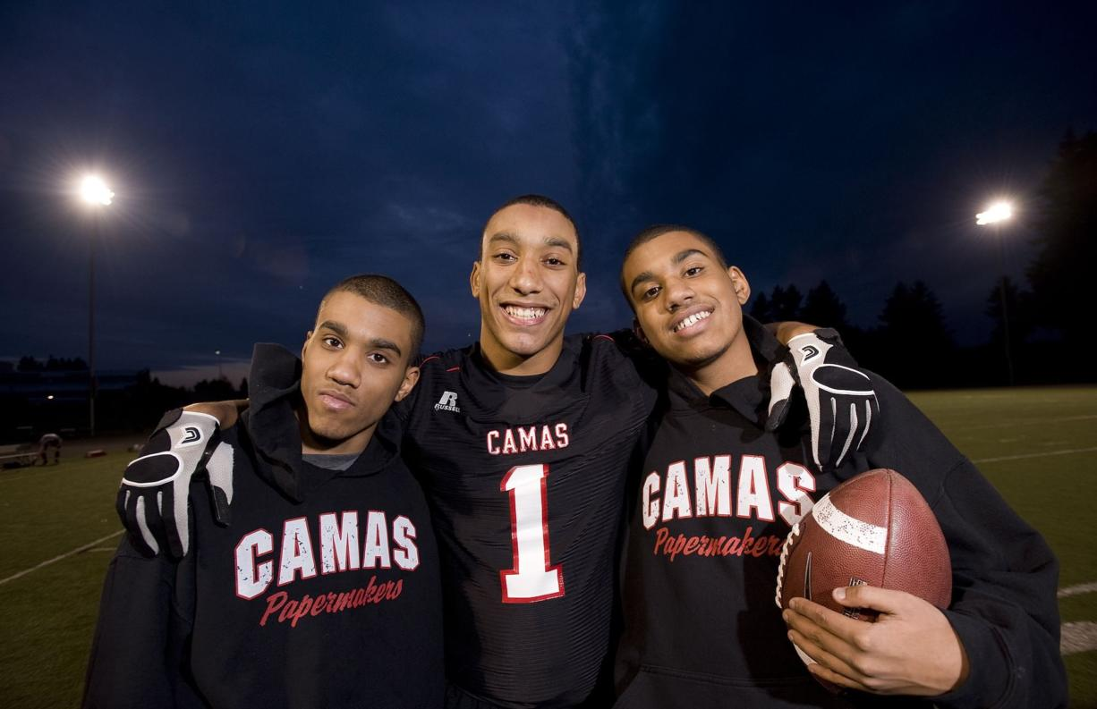 Jonathan Warner, center, poses with his autistic twin brothers, Christian, left, and Austin, at Camas High School.