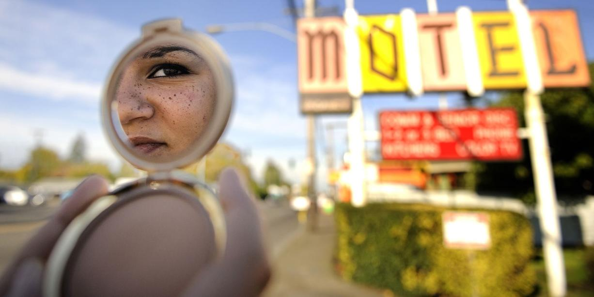 """Jennifer,"" a Clark County teen formerly involved in prostitution, watches over Portland's Southeast 82nd Avenue. The motel in the background was once used by prostitutes including Jennifer; it's now under new management and Portland police say it has not been named in any recent reports of sex trafficking."