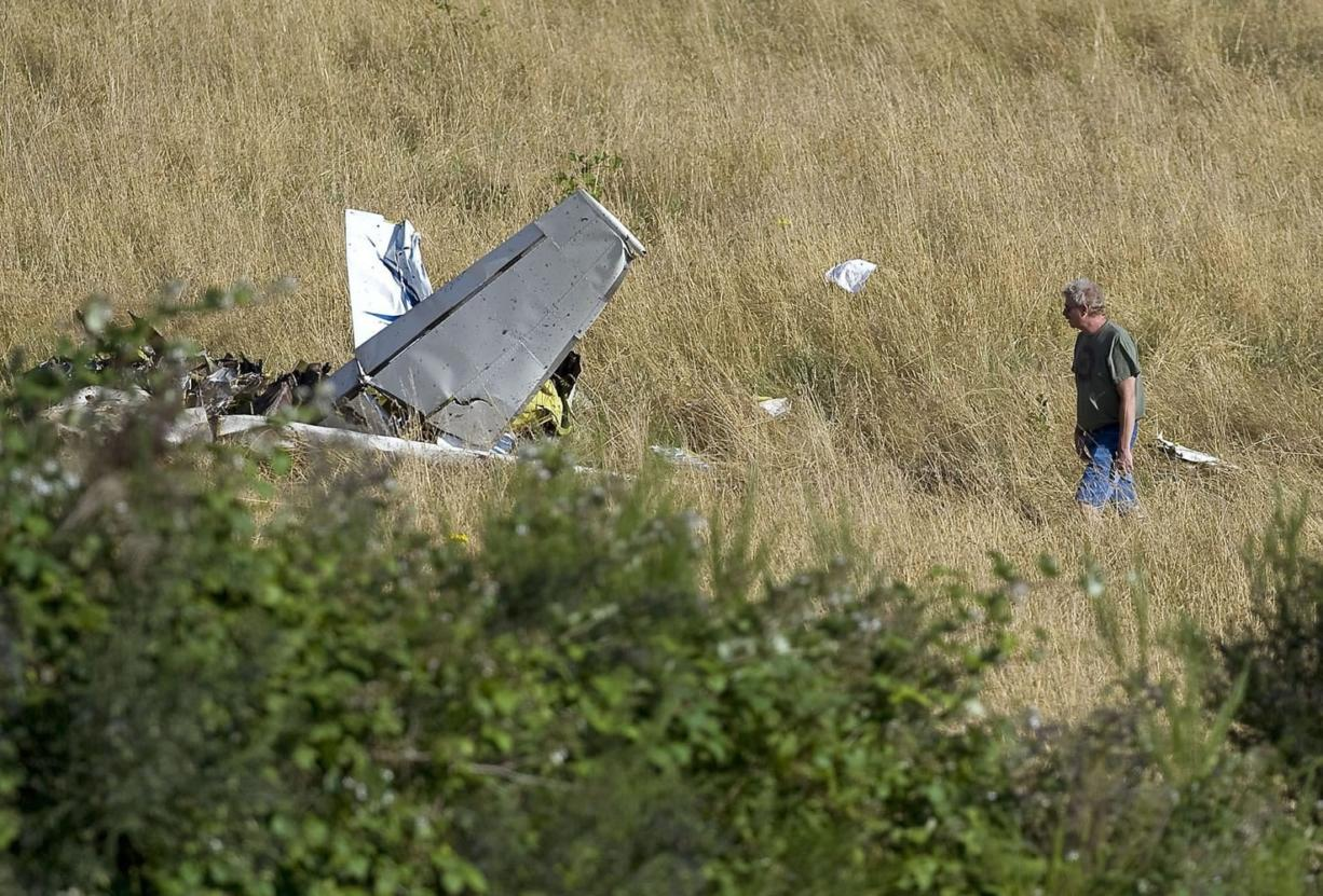 An investigator examines the wreckage of a light plane near Fern Prairie, north of Camas, Wednesday.