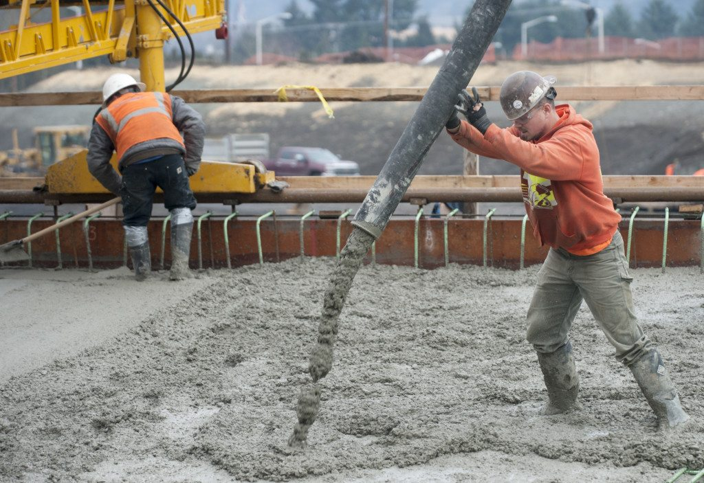 A Construction Worker Controls Concrete Flow While Another Rakes The Thursday As They Wor