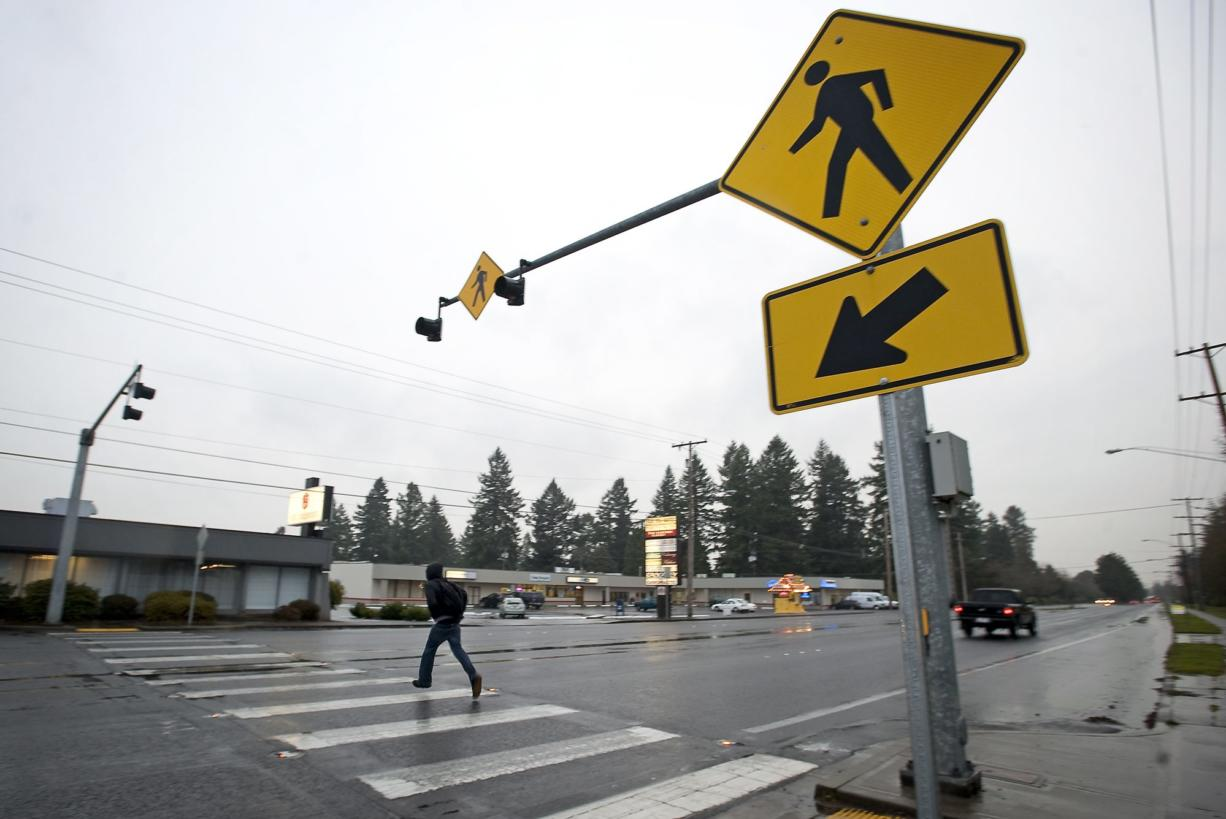 A man runs across Mill Plain Boulevard on Jan. 4 where a pedestrian had been fatally injured by a car on Dec. 29. The crosswalk is slated for a safety upgrade this year.
