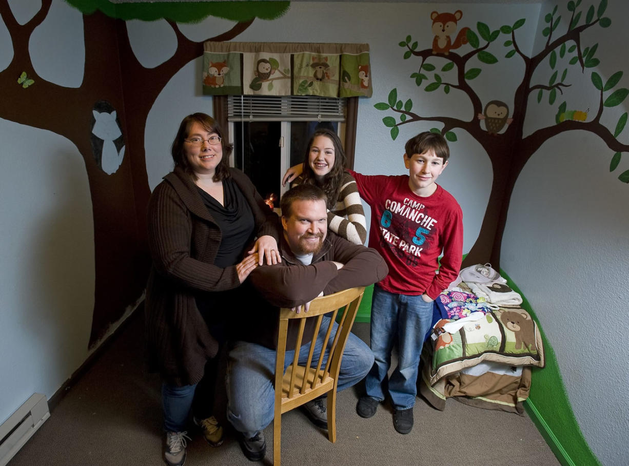 Mark and Rebecca Jenks pose for a portrait with Rebecca's children, Tamara Emler, 15, and Brandon Emler, 13, inside a room prepared for their adopted baby.