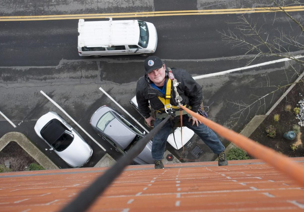 Greg Guetlin is seen on the job in downtown Vancouver. Guetlin is employed washing windows as well as the exteriors of buildings, including many multistory structures.