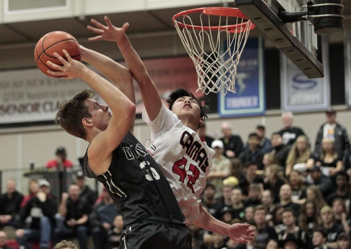 Union forward Denis Kirichenko, left, shoots against Camas' Bryan Nguyen, right. Union held off the Papermakers 58-54 to take a three-game lead in the 4A Greater St. Helens League.