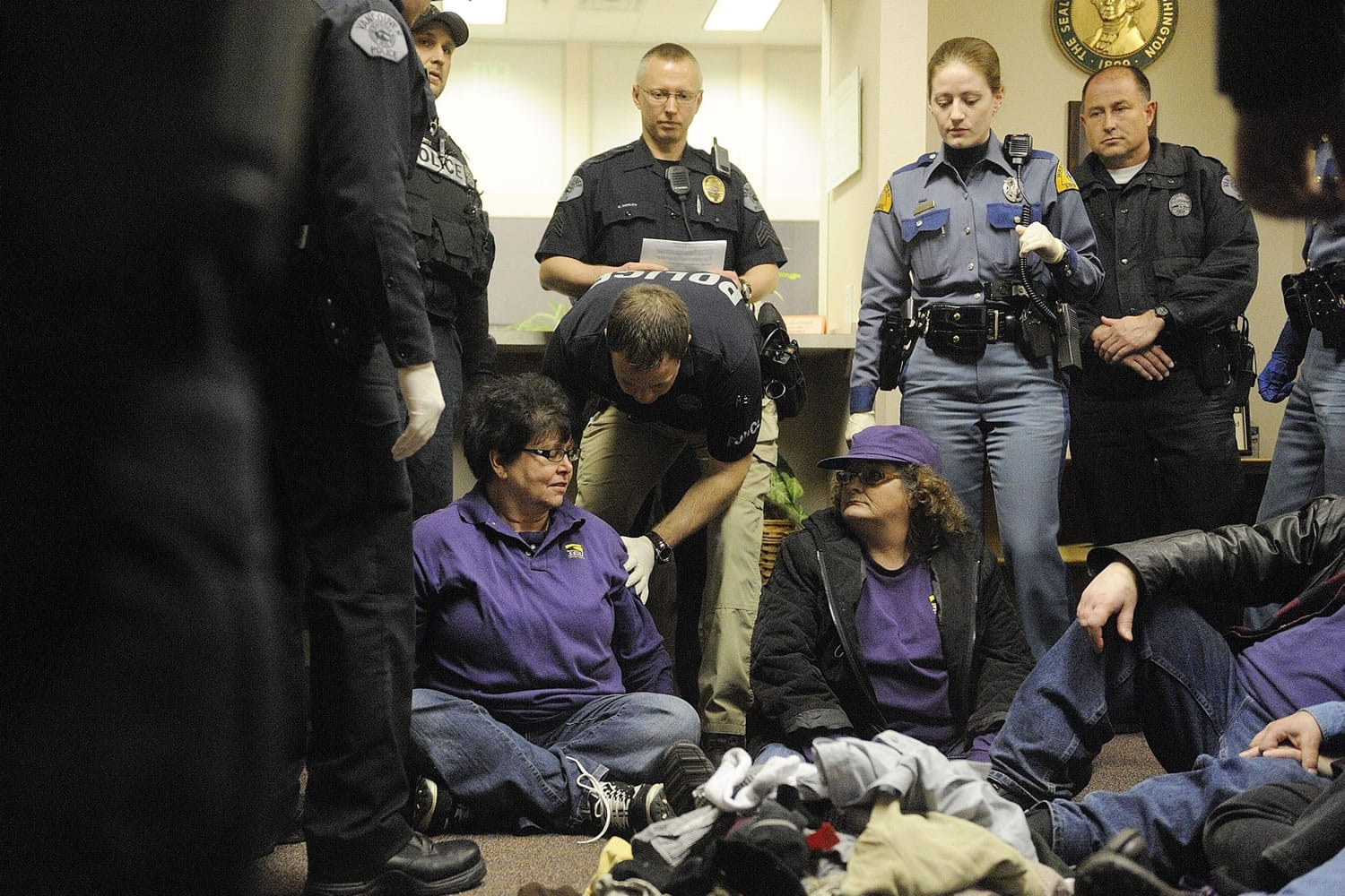 Vancouver police and Washington State Patrol officers arrest Pamela McCarty, left, a home care provider from Centralia, Tuesday for suspicion of misdemeanor trespassing after she and other protesters refused to leave the state Office of Administrative Hearings in Vancouver.