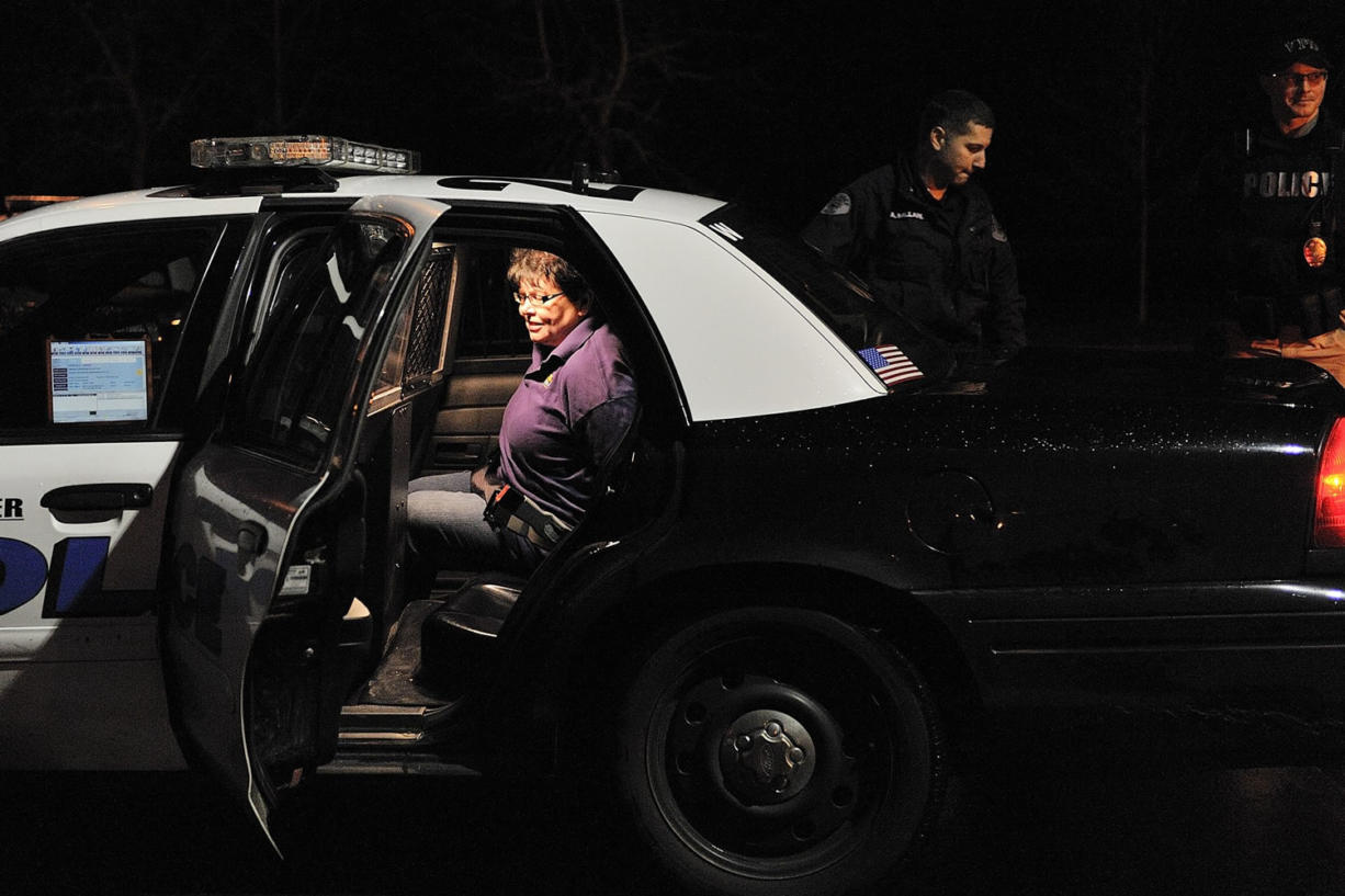 Vancouver police and Washington State Patrol officers place protester Pamela McCarty in a police vehicle.