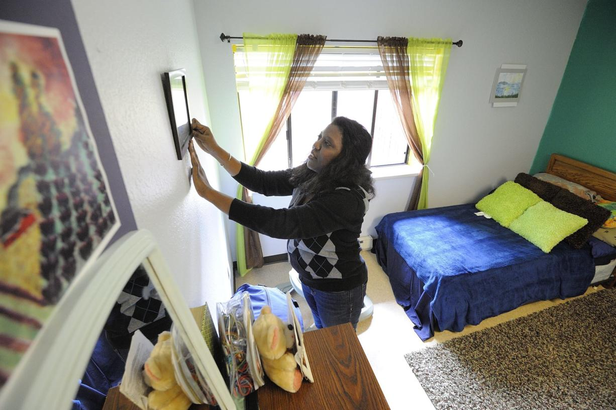Sonja McKenzie hangs a family photo in the bedroom at the Share Orchards Inn homeless shelter where she and her four children lived last year.