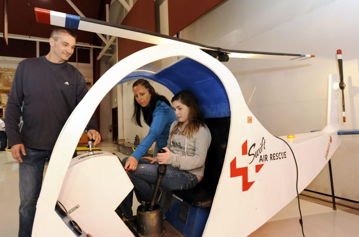 Victoria Quintero, seated, with her parents Tanya Quintero and Jaider Quintero, left, examines a hands-on helicopter display at Pearson Air Museum.