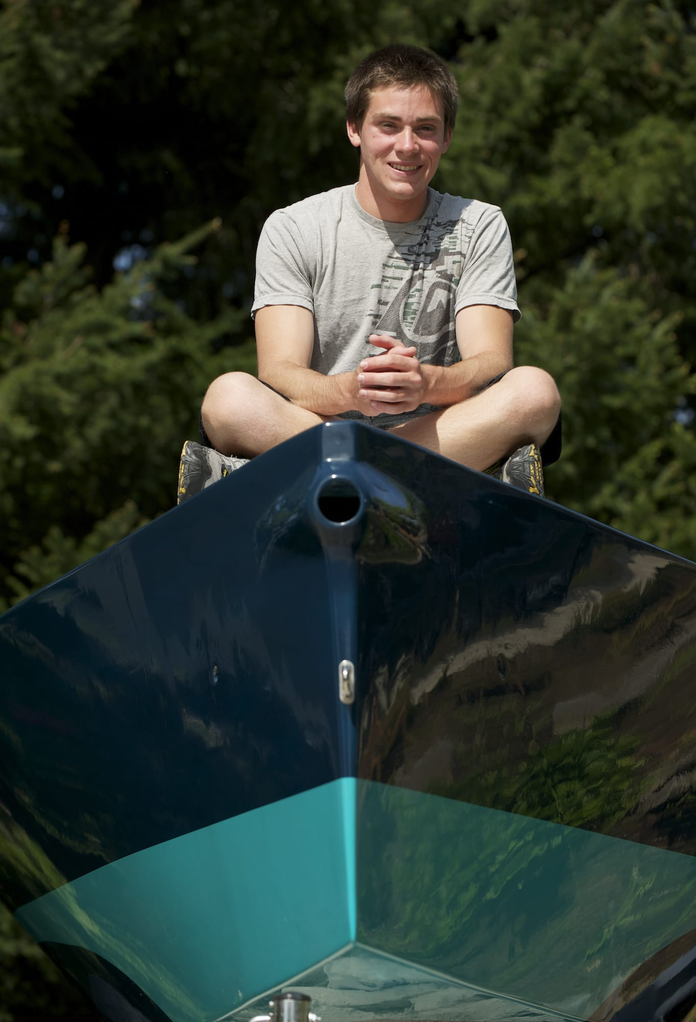 Camas High School senior Stephen Moran sits atop his i550 racing sailboat Friday afternoon. Moran spent seven months and 300 hours building the boat for his senior project.