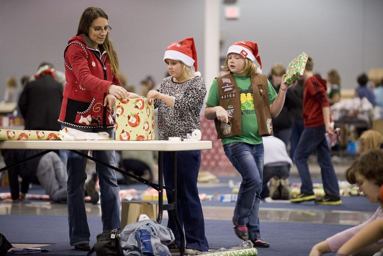 Volunteers, from left, Debbie LaPier, Delainey Phelps, 8, and Sophia Davis, 8, both from Girl Scout Brownie Pack 42150, wrap presents for needy families, Thursday, December 15, 2011.