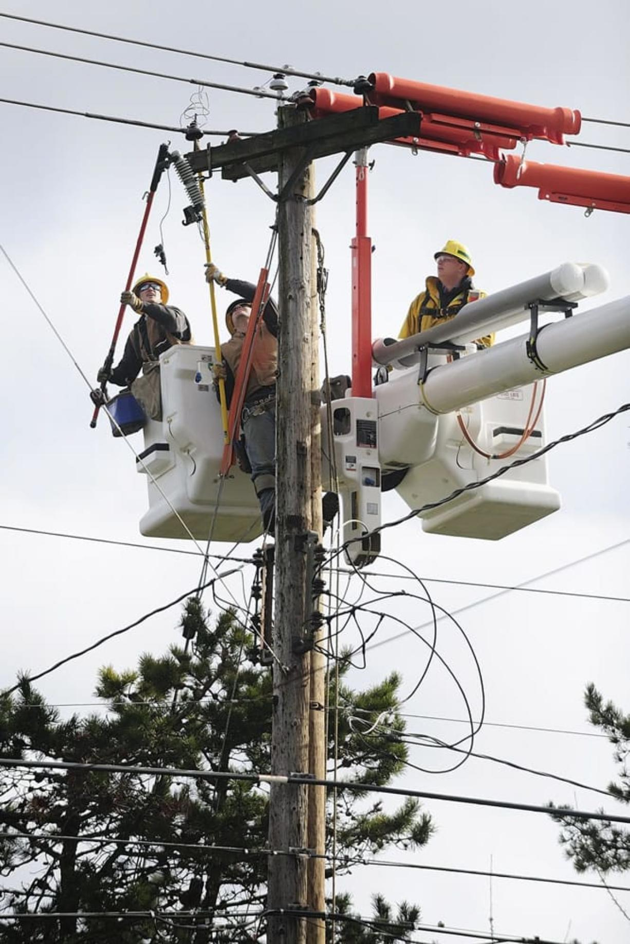 Clark Public Utilities linemen Kenny Cudd, from left, Tommy Jensen and Zach Muonio move conductors as they prepare to replace a power pole in use since 1956. The three lineman are part of a five-person crew, which is required by state law.