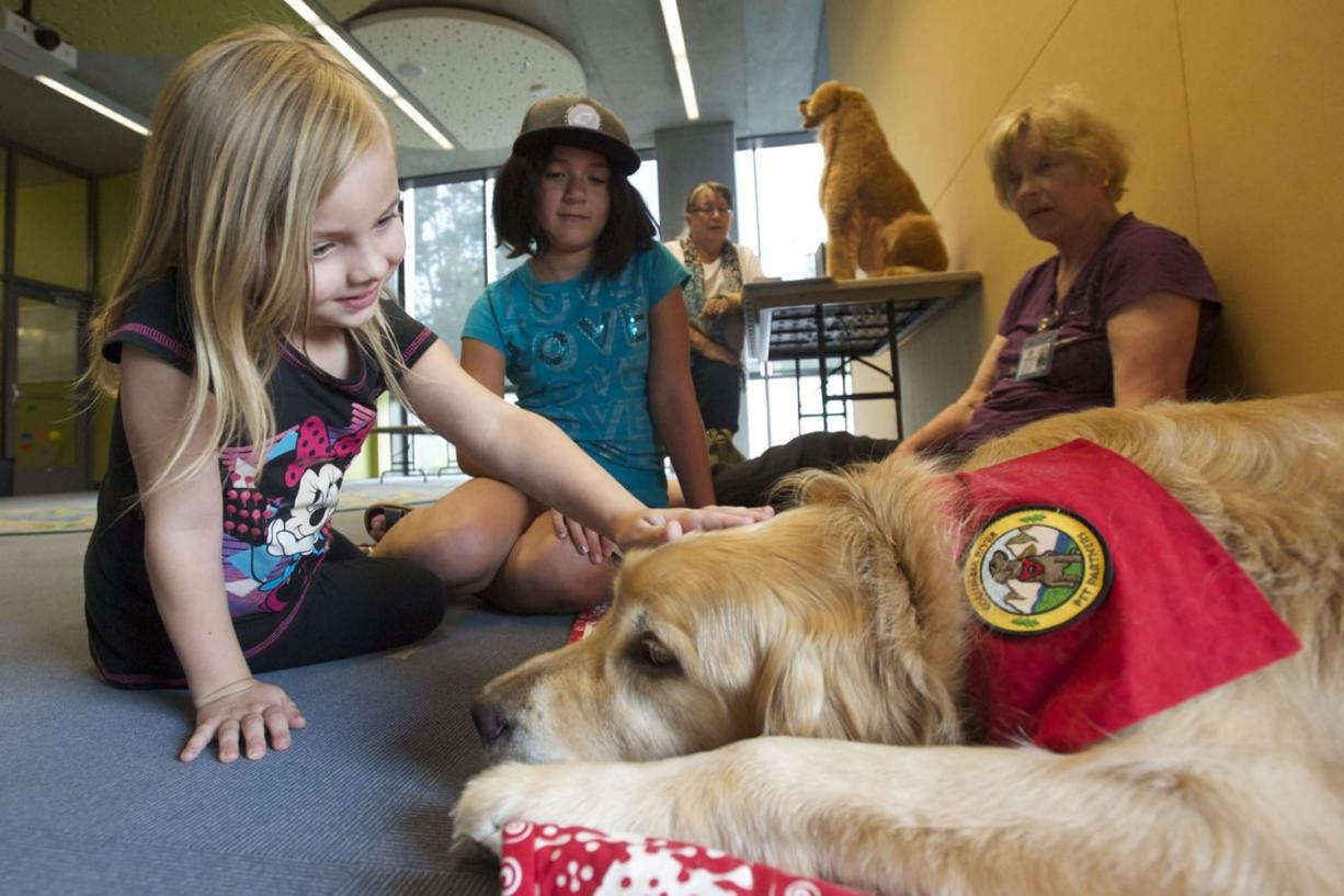 Lola Fuller, 6, left, and Sofia Arellano, 9, meets Columbia River Pet Partners therapy dog Crunch, a golden retriever. The children practiced their reading skills by reading to him at the Vancouver Community Library on Aug. 13, 2014. Therapy animal handler Michael Kay Richardson watches at rear.