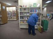 """Dolly Jendro, of Washougal, looks over the new book selections Tuesday at the Vancouver Mall Community Library. The Fort Vancouver Regional Library District will reduce the space and services at the mall branch in 2013. """"It will have serious repercussions,"""" Jendro, 81, said."""