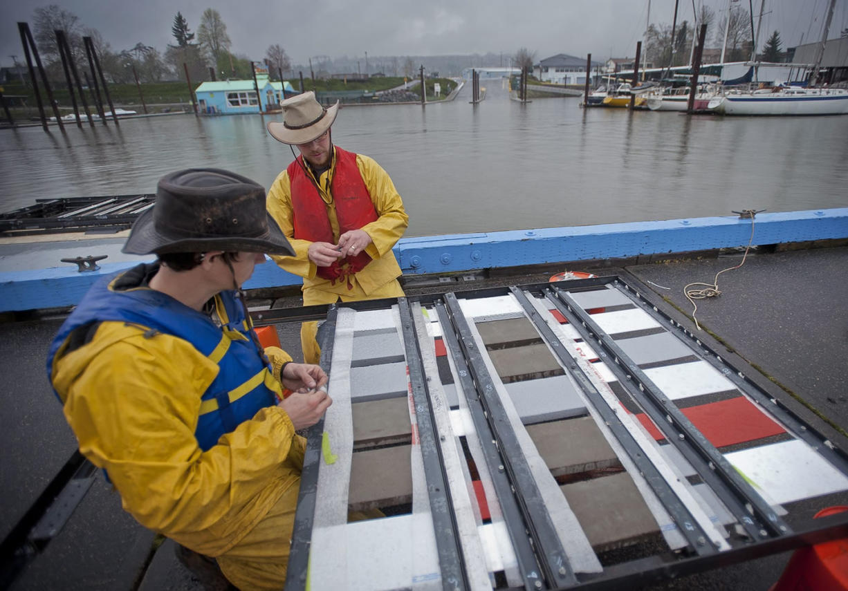 Steve Wells, right, a Portland State University research assistant, and PSU student Leonard Caldwell attach treated tiles to a metal frame that will be submerged and fastened to a dock at the Port of Camas-Washougal.