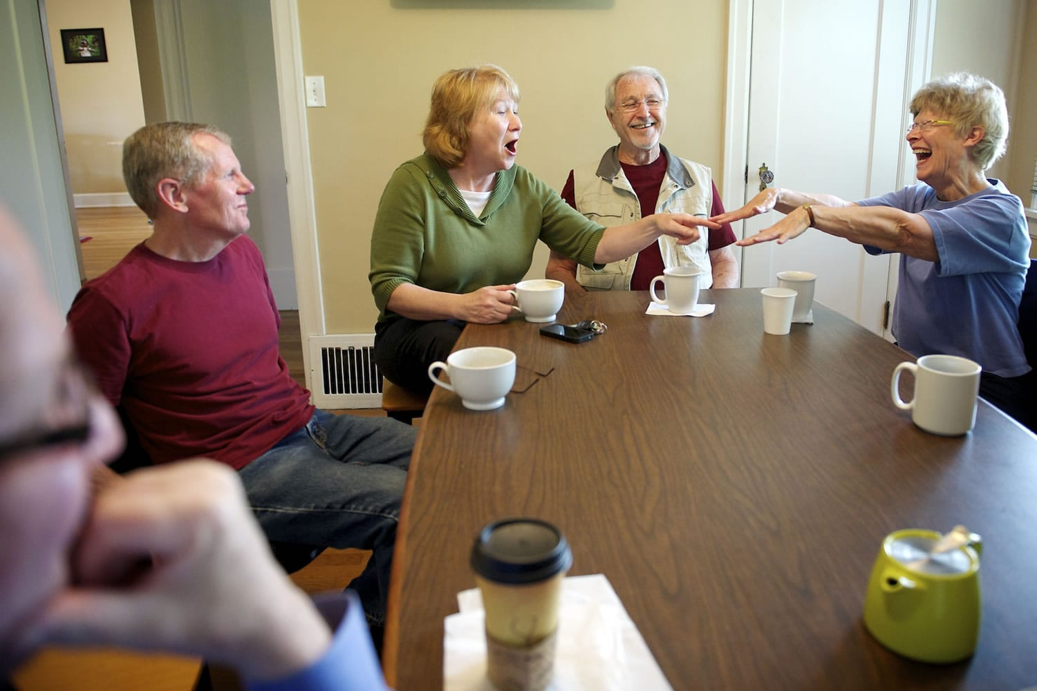 Anne McEnerny-Ogle, left, wearing green, shares a light hearted moment with Andrea Powley, right, wearing blue, as her husband, Randall Powley, center, and Terry Ogle, Anne's husband, chat during a neighbors meeting at Latte Da Coffee House.