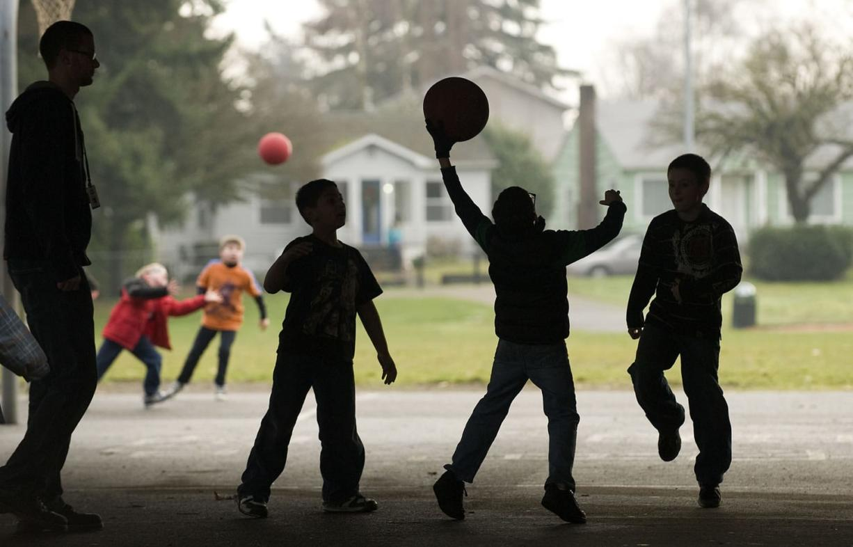 Children in the Vancouver-Clark Parks & Recreation's Kids First After School program play wall ball at the Washington Elementary School playground Monday.