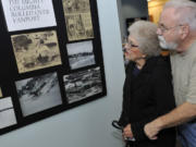 Luanne (Wolfe) Barnes, a survivor of the 1948 Vanport Flood, looks at old photos with her husband, Ed Barnes, at Saturday's opening of the Vanport Flood Exhibit at the Water Resources Education Center in Vancouver.