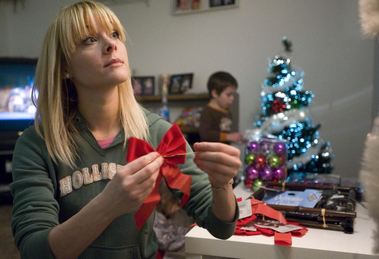 Erica Conger decorates her new apartment for Christmas with her children Maddox, 4, and Ella, 2 on Monday. The Army veteran was set up in the subsidized apartment with help from the nonprofit Partners in Careers.
