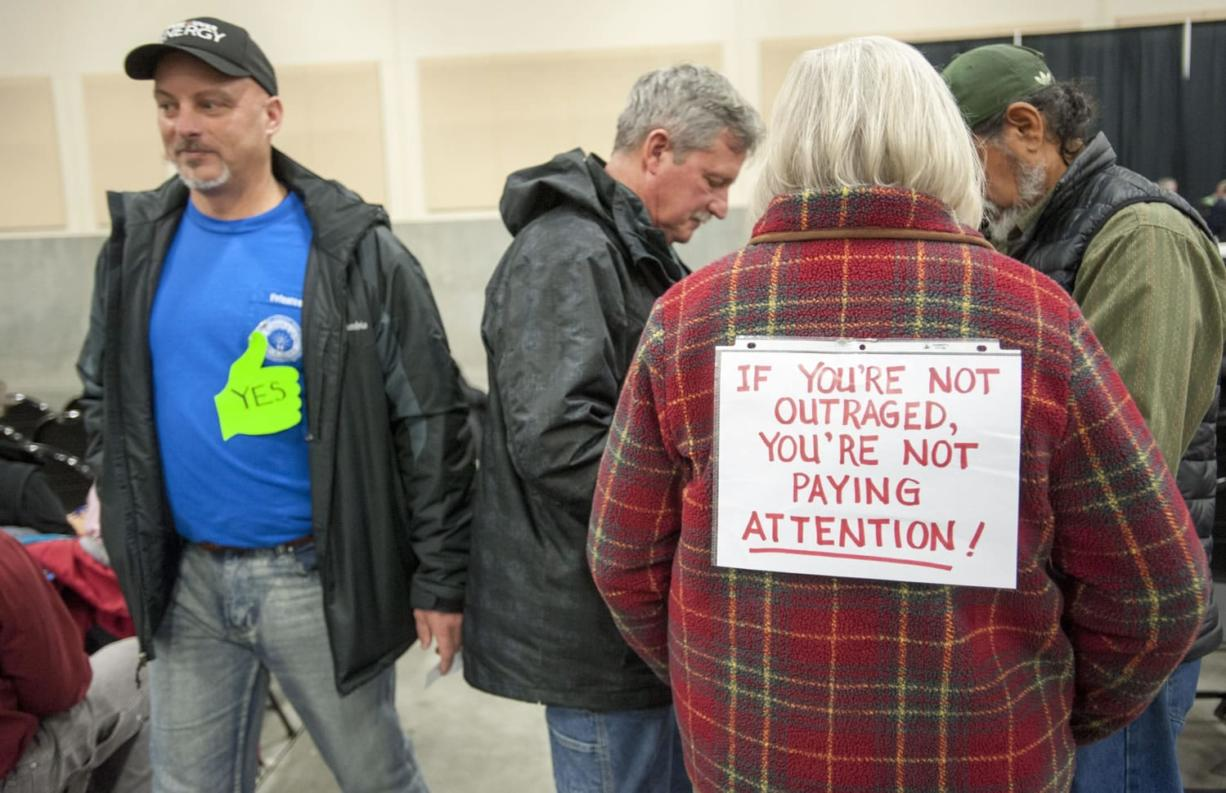 A pro-terminal supporter walks past Edie Cotton, left, who had a sign on her back opposing the terminal, as they attended the Energy Facility Site Evaluation Council's hearing Jan. 12 in Ridgefield on the construction of an oil terminal in Vancouver.