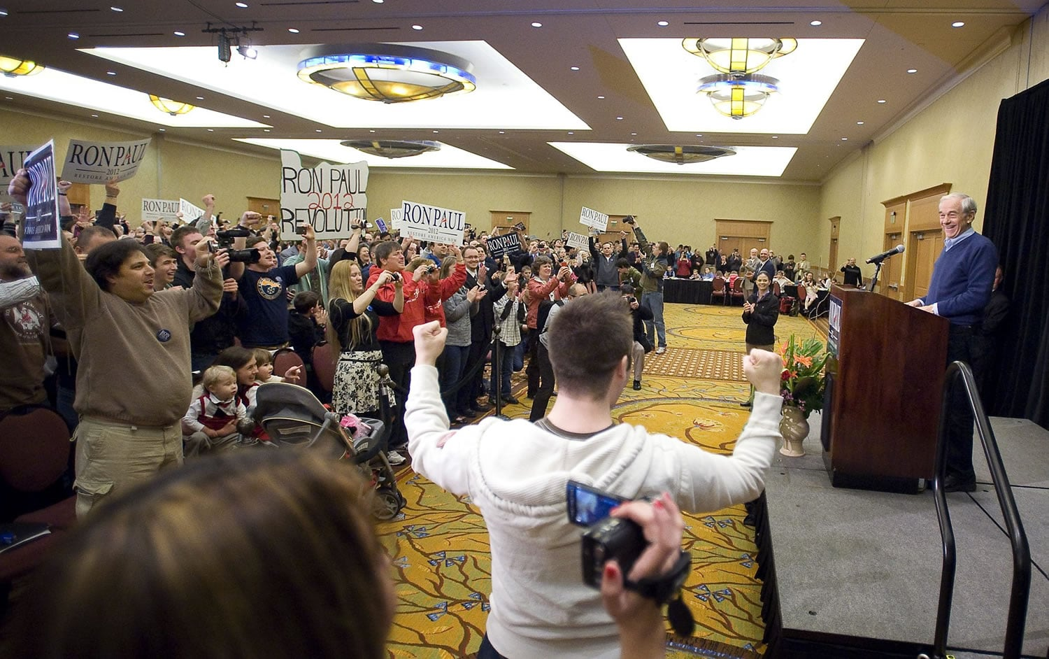 "Republican presidential candidate Ron Paul takes the stage during a rally at the Hilton Vancouver Washington on Thursday. The crowd waved signs and chanted ""President Paul"" to show their support. At top, Paul meets with members of the press after speaking at the rally."