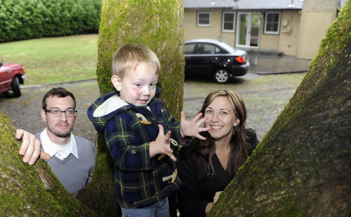 Two-year-old Zephyr Thackeray shows off his new climbing tree with the help of his parents, Ian Thackeray, left, and Tara Thackeray, right, in the back yard of their newly purchased Vancouver starter home.