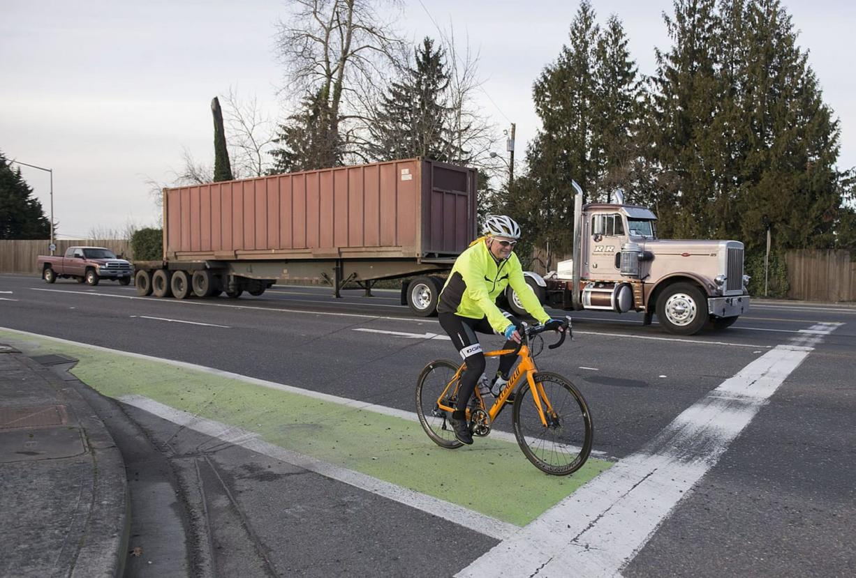 A cyclist traveling on state Highway 501 travels in a green bike lane near St. Francis Lane in Vancouver.