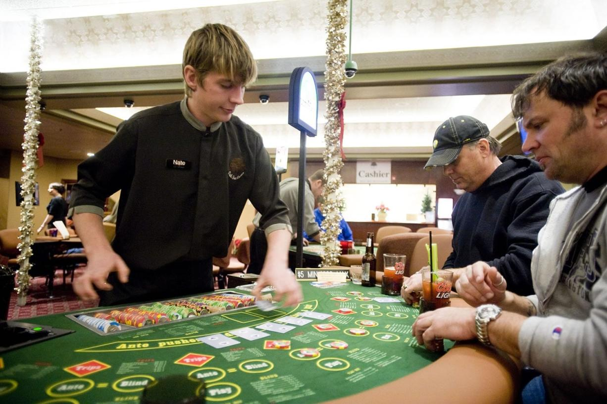 Kevin Hildebrandt, center, and Vaughn Kercher, both from Seattle, play poker at dealer Nate Wheatley's table at the Oak Tree Casino on Saturday, the Woodland card room's opening day. The state has not conducted a study on problem gambling since 1999, even as gambling has mushroomed into a $2.5-billion industry.
