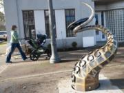 """A woman pushes a stroller Wednesday past """"The Visitor,"""" a new steel sculpture by Seattle artist Matthew Dockrey at West 23rd and Main streets."""