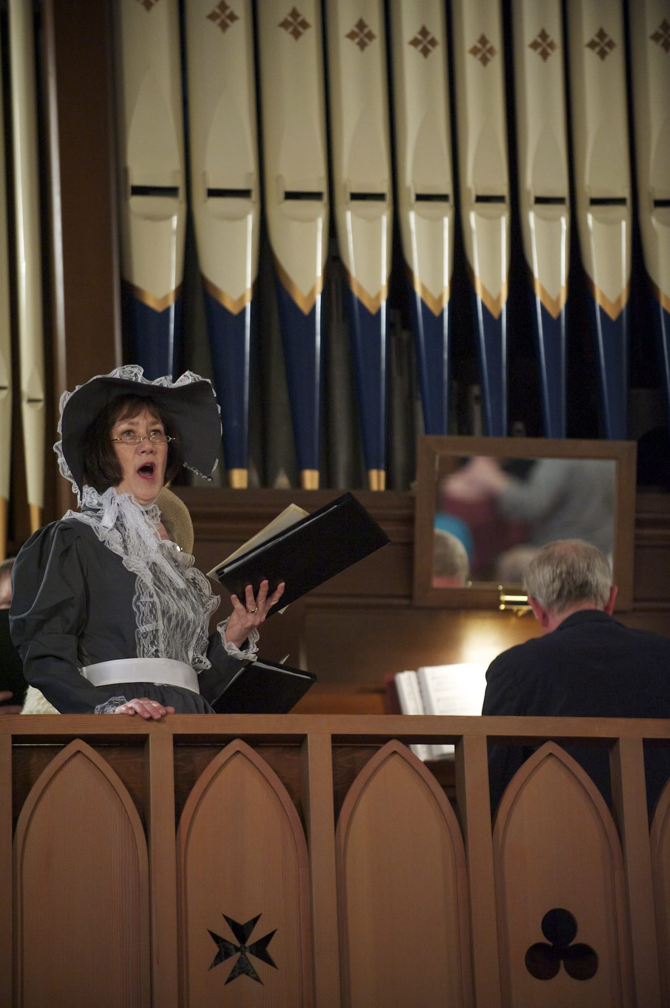 St. Luke's Episcopal Church choir member Pam Goodlett sings from the choir box as the church celebrates its 152nd anniversary on Sunday. The congregation used the original prayer book from 1789 and many parishioners dressed in period clothing.
