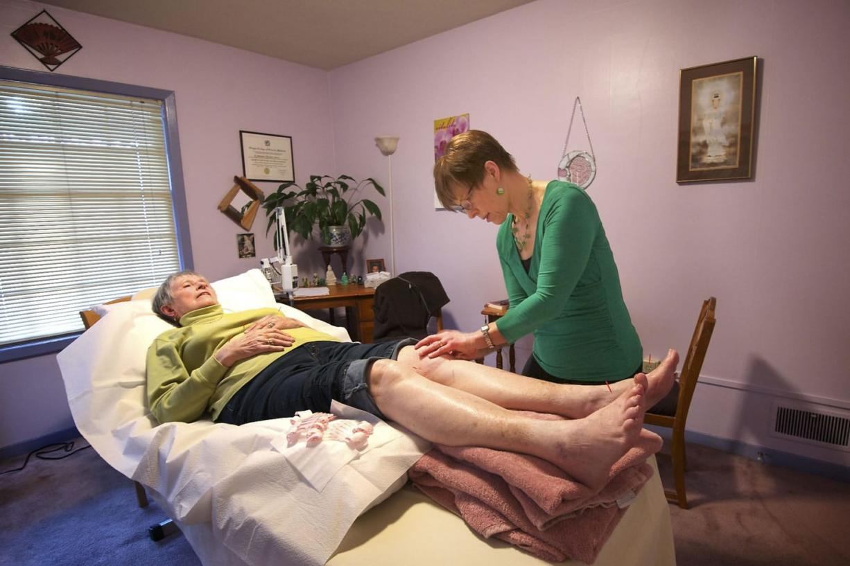 Jowanna Harman-Stever, right, of New Harmony Health in Vancouver, provides acupuncture treatment to patient Virginia Barber, 80, recently. Barber has peripheral neuropathy, a progressive nerve condition, and uses alternative techniques such as acupuncture to help alleviate the pain.