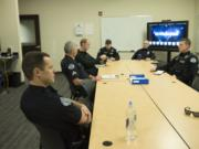 Officer David Krebs, left, listens during a squad briefing Friday afternoon at Vancouver Police Department's West Precinct. The police chief has proposed adding 42 more officers to the department, which now has 190 officers.