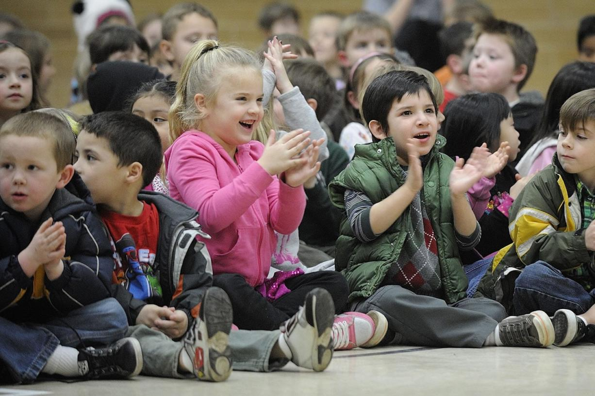 """Elyse Krout, center in pink, and Noah Alfter, wearing green, kindergartners at Pleasant Valley Primary School, cheer for the cast of """"Hansel and Gretel."""""""