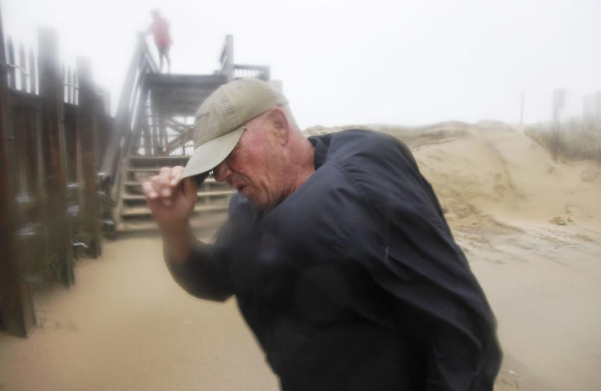 Summer resident Jody Bowers braces himself from a blast of sand and driving rain as he makes his way to the beach in Kill Devil Hills, Outer Banks, N.C., Saturday as Hurricane Irene reaches the North Carolina coast.
