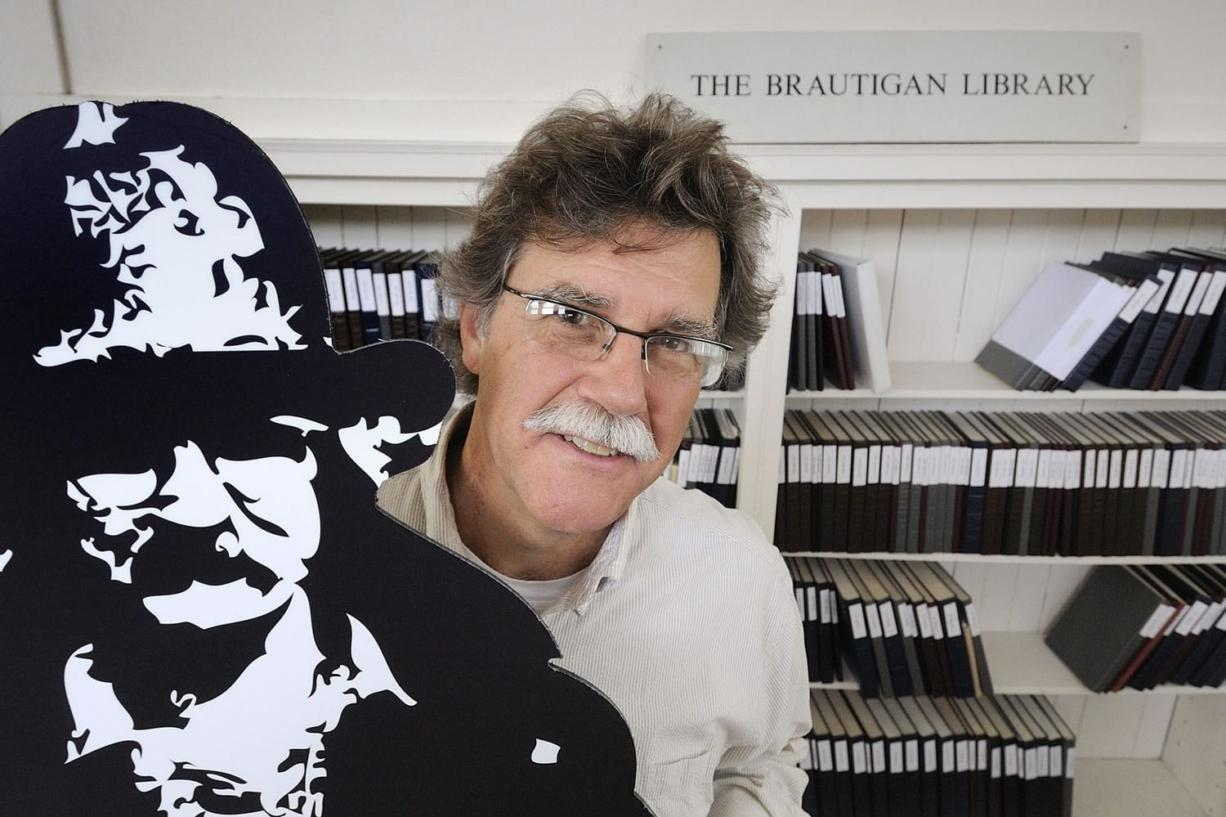 John F. Barber, with the Creative Media & Digital Culture Program at Washington State University Vancouver, holds a cardboard cutout next to a display of The Brautigan Library at The Clark County Historical Museum.