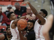 Colorado's Tre'Shaun Fletcher, center, goes after a rebound against Washington State's Ny Redding, left, and Robert Franks during the first half of an NCAA college basketball game Saturday, Jan. 23, 2016, in Pullman, Wash.