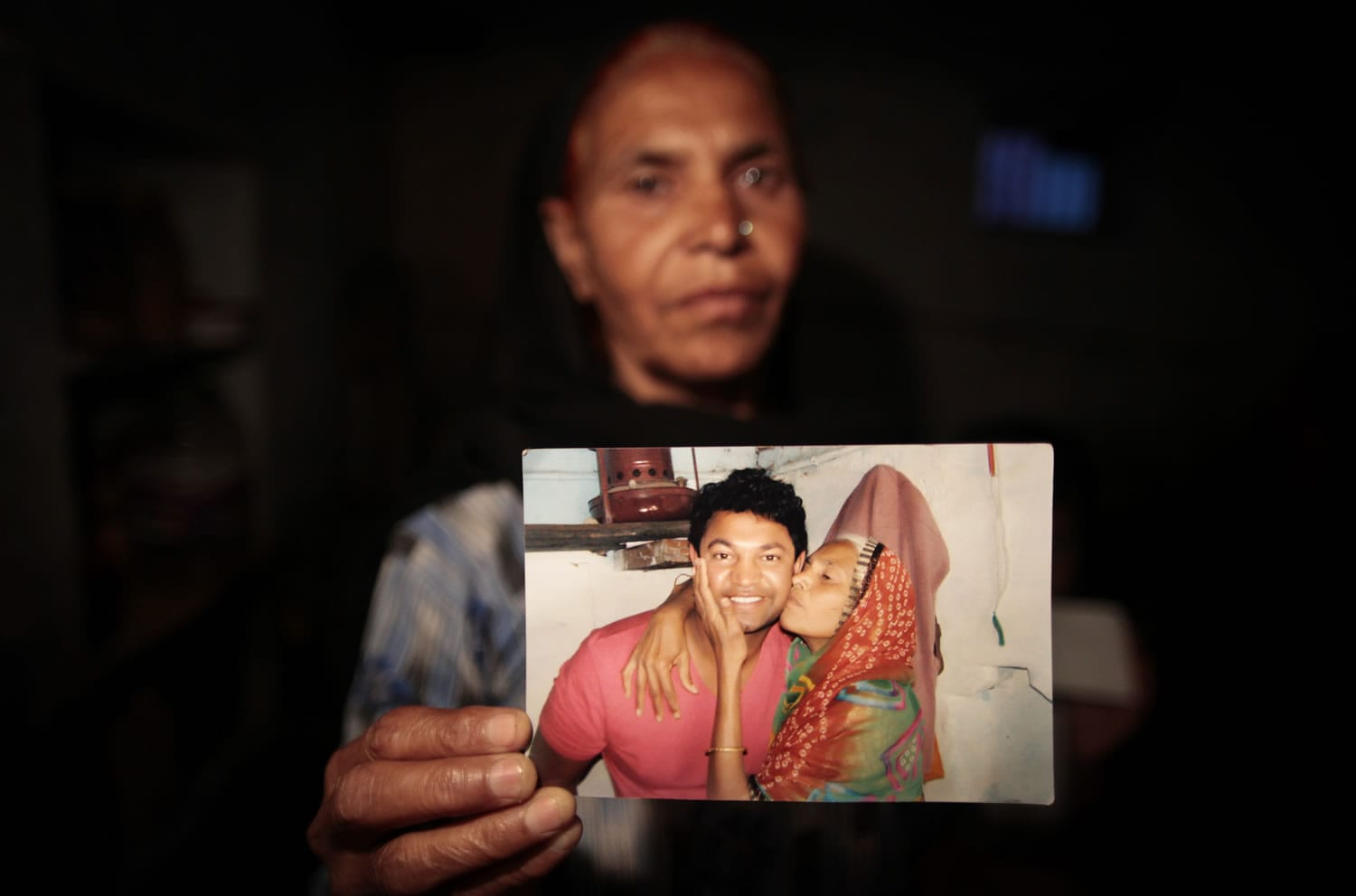 In this May 10, 2012 photo, Fatima Munshi, mother of Saroo, holds up a photo from their reunion in February 2012 at her home in Khandwa, India. Living in Australia, Saroo Brierley, 30, was reunited with his biological mother, Munshi, 25 years after an ill-fated train ride left him an orphan on the streets of Calcutta.