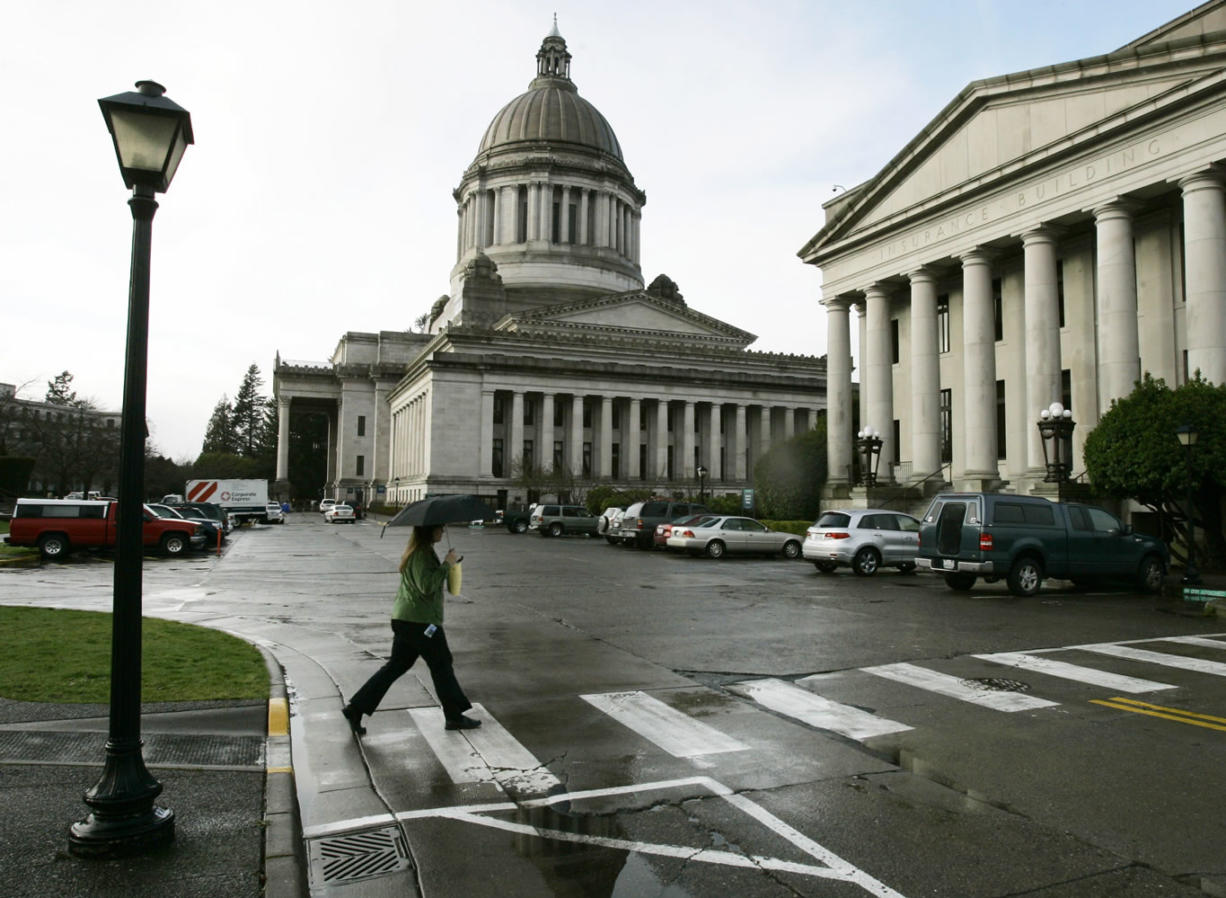 A pedestrian uses an umbrella as she crosses the street at the Capitol in Olympia.