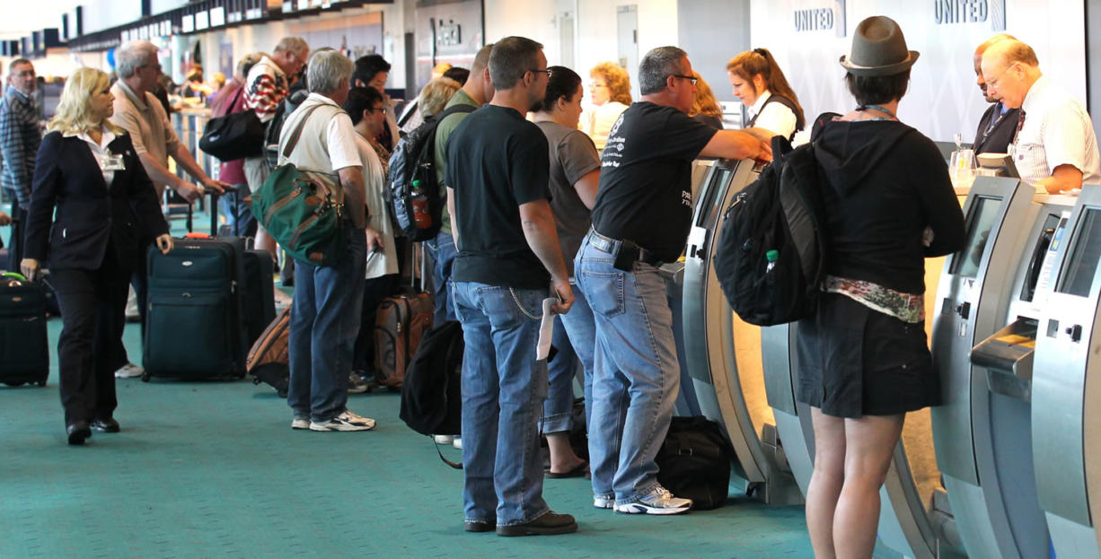 Travelers gather at the ticket counter at Portland International Airport.