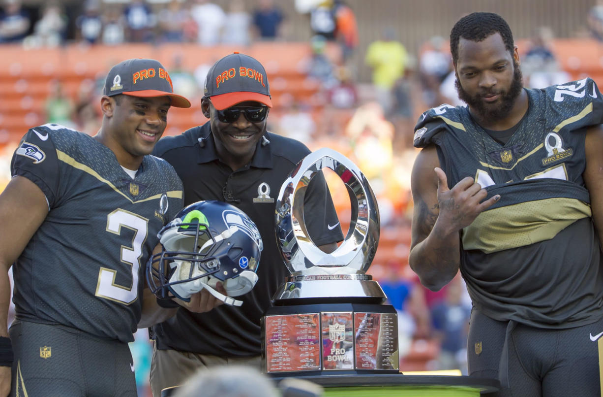 Michael Irvin, Pro Bowl legend team captain and Pro Football Hall of Famer, center, takes a photo with Seattle Seahawks quarterback Russell Wilson (3), who was named the offensive player of the game, and defensive end Michael Bennett, of Team Irvin, right, after the NFL Pro Bowl football game, Sunday, Jan. 31, 2016, in Honolulu. Team Irvin won 49-27. (AP Photo/Eugene Tanner)