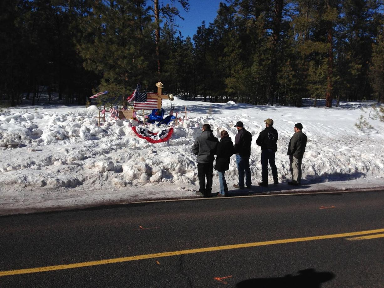Mourners gather Sunday on U.S. Highway 395 at a roadside memorial where rancher LaVoy Finicum was shot and killed Tuesday night in a confrontation with the FBI and Oregon State Police near Burns, Ore. (Nick K. Geranios/Associated Press)