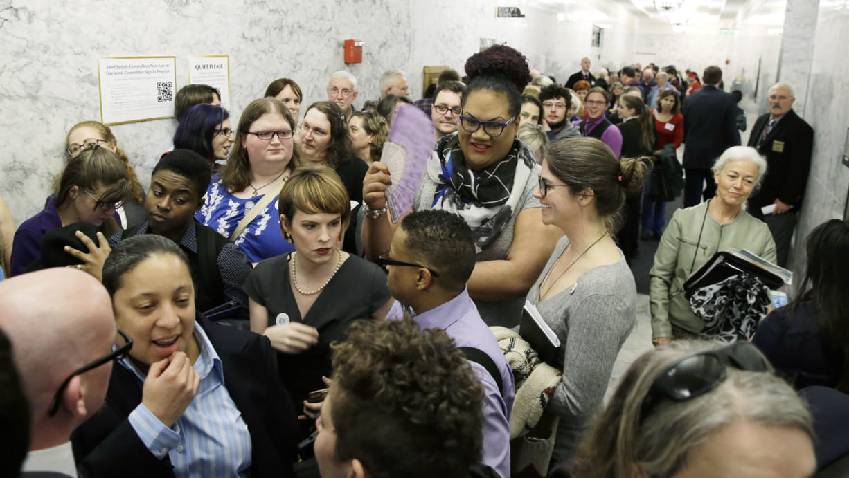 People pack a hallway outside a Washington Senate hearing room,  Jan. 27 at the Capitol in Olympia, as they wait to listen to public testimony regarding a bill that would eliminate Washington's new rule allowing transgender people use gender-segregated bathrooms and locker rooms in public buildings consistent with their gender identity. (AP Photo/Ted S. Warren)