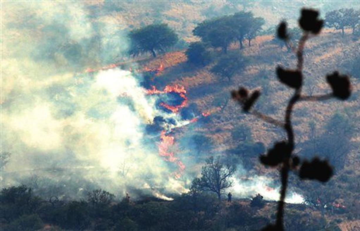 Firefighters create a burnout to protect homes in the Ash Canyon area near Sierra Vista, Ariz., on Monday, June 13, 2011. (AP Photo/Sierra Vista Herald, Beatrice Richardson)