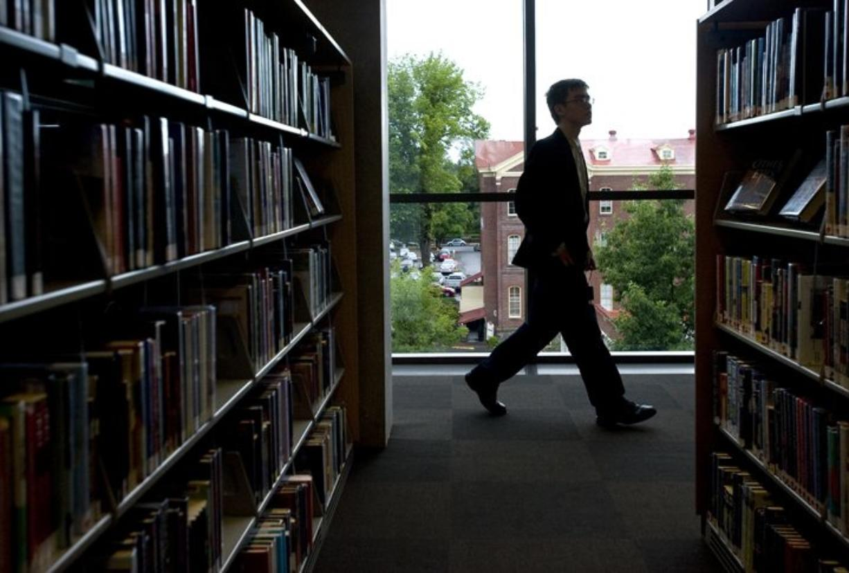 A patron walks past rows of books on the fifth floor during the grand opening of the Vancouver Community Library on Sunday July 17, 2011.