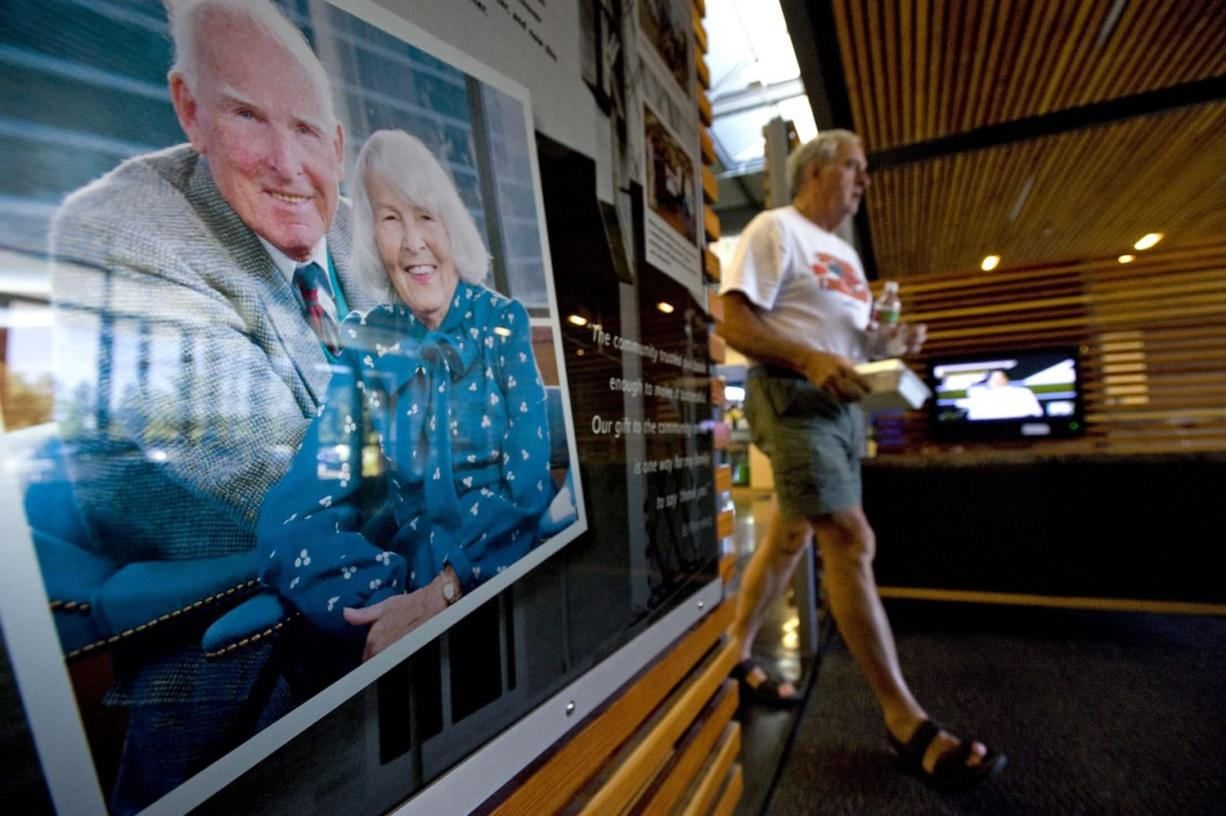 Rolf Adams, of Vancouver, walks past a photograph of Ed and Mary Firstenburg inside the lobby of the Firstenburg Community Center on Aug. 23, 2010.