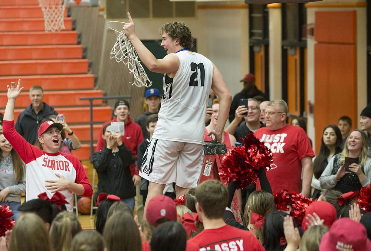 Union's Nico Bricker (21) celebrates the win with teammates and fans Tuesday evening, Feb. 16, 2016 at Battle Ground High School.